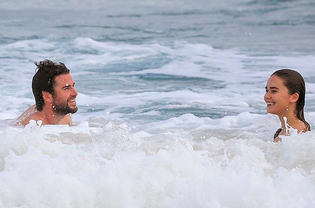 Cặp đôi nô đùa với những con sóng lớn tại một bãi biển vắng vẻ.