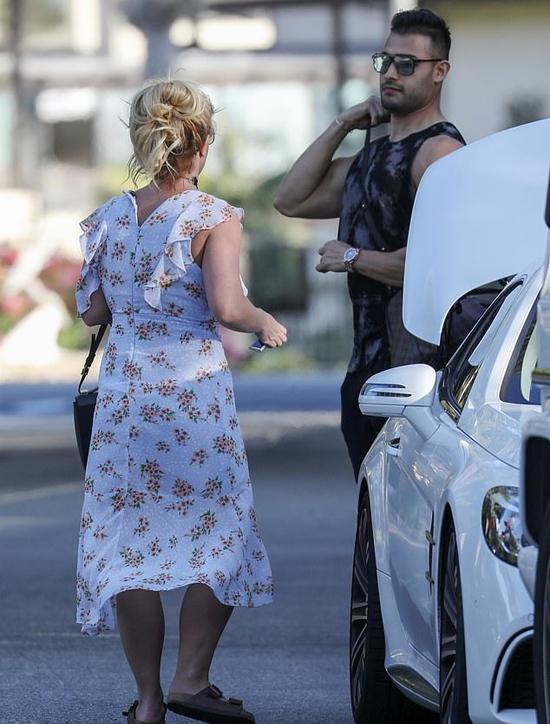 Britney và chàng người mẫu Sam Asghari mặc đồ đơn giản khi đến khách sạn. Nữ ca sĩ nhạc pop xỏ đôi dép lê đã cũ và mặc chiếc váy hoa bánh bèo không được là lượt cẩn thận. Britney vốn là người ăn mặc xuề xòa, thường ra đường với gương mặt mộc và đầu tóc rối bù.