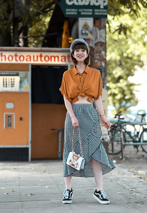 Còn chân váy midi xếp nếp thì lại bổ sung nét nữ tính cho tổng thể.