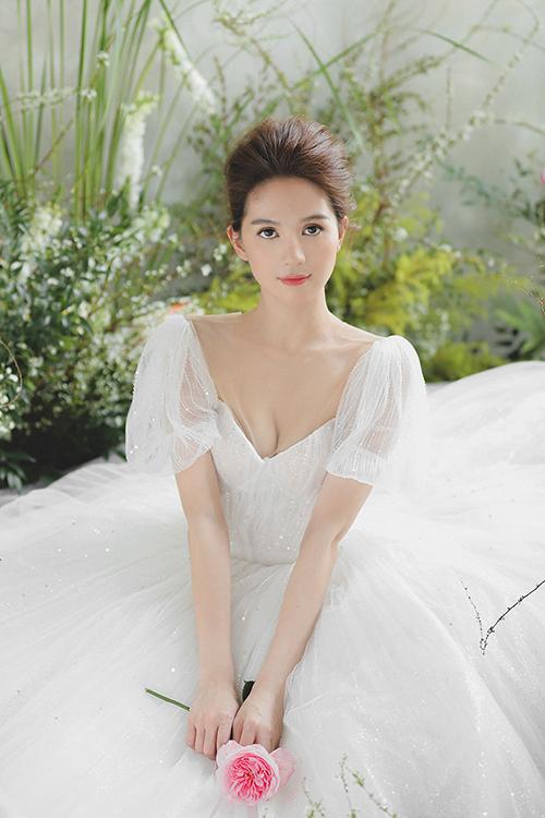 Những hạt đá được đính kết dọc thân, tạo độ bắt sáng tự nhiên cho mẫu váy ball-gown. Lối makeup được lựa chọn cho Ngọc Trinh là tông hồng đào kiểu Hàn Quốc,kiểu tóc chải phồng, giúp tôn nhan sắc thanh tú, vẻ ngây thơ của người đẹp.