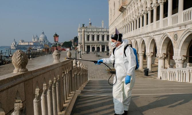 Một nhân viên y tế phun khử trùng cây cầu Ponte della Paglia trên quảng trường St. Mark ở thành phốVenice, Italy. Ảnh: Reuters.
