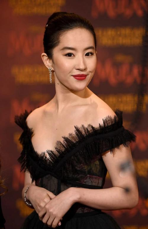 Trên thảm đỏ buổi ra mắt phim Mulan, Lưu Diệc Phi diện váy đen trễ vai, cổ xẻ sâu và khoe nhan sắc đẹp rạng ngời. Cô