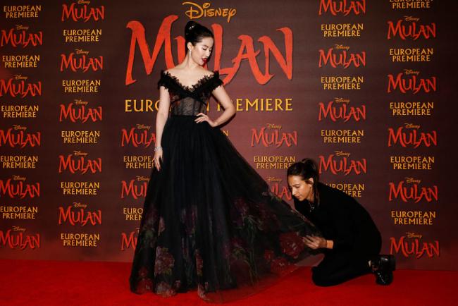 Lưu Diệc Phi được hỗ trợ chỉnh sửa váy áo trên thảm đỏ.