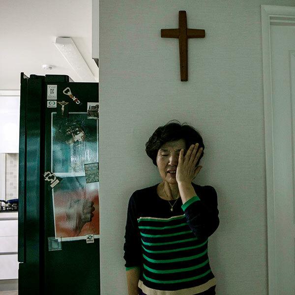 Một phụ nữ bật khóc tại nhà riêng ở Goyang, Hàn quốc tuần trước sau khi không thể khuyên nhủ con gái rời Tân Thiên Địa. Ảnh: NY Times.