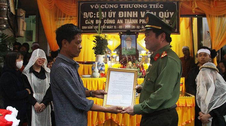Giám đốc Công an tỉnh Ninh Bình trao quyết định thăng hàm cho thân nhân thiếu tá Đinh Văn Quý.