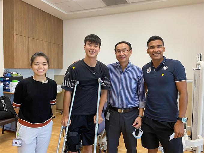 Duy Mạnh chụp ảnh cùng bác sĩ Singapore và bác sĩ Vũ Thành Luân (ngoài cùng bên phải) trong buổi tái khám sau phẫu thuật. Ảnh: DM.