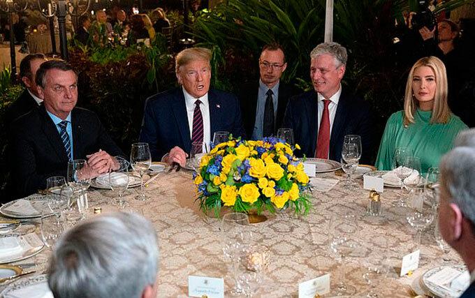 Tổng thống Mỹ Donald Trump ngồi ăn tối với Tổng thống Brazil Jair Bolsonaro (bìa trái) và con gái Ivanka Trump (bìa phải) tại Mar-a-Lago hôm 7/3. Ảnh: AFP.