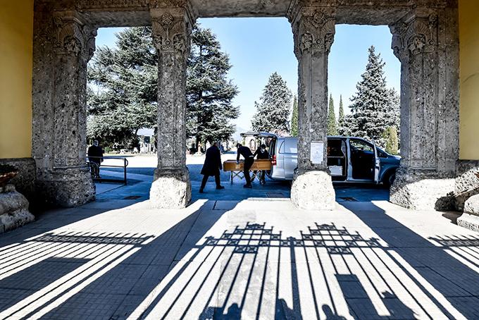 Những nhân viên tang lễ chở quan tài về tập kết ở một nghĩa trang tại thành phổ Bergamo, Italy. Ảnh: NYT.