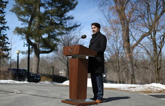 Thủ tướng Trudeau đứng cách xa phóng viên khi phát biểu tại Rideau Cottage ở Ottawa hôm 16/3. Ảnh:AFP