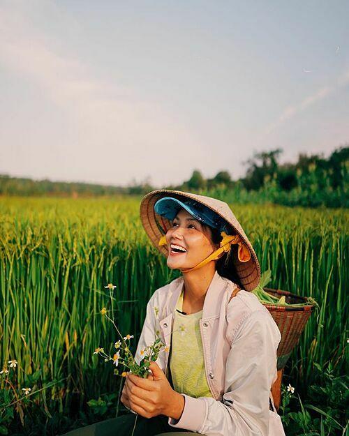 Chiều hoàng hôn nắng chiếu lung linh, HHen Niê chia sẻ về bức ảnh của mình. Người đẹp Ê Đê mặc trang phục giản dị, đội nón lá ra thăm cánh đồng. Bạn trai tin đồn cũng về cùng cô.