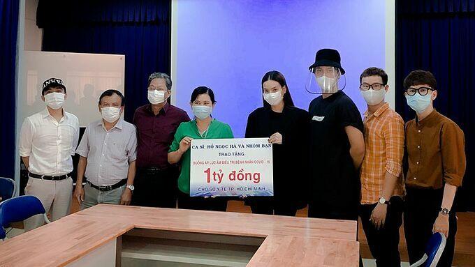 Hồ Ngọc Hà, Lý Quí Khánh (thứ năm và sáu từ trái qua) trao số tiền cho đại diện Sở Y tế TP HCM, chiều 17/3.