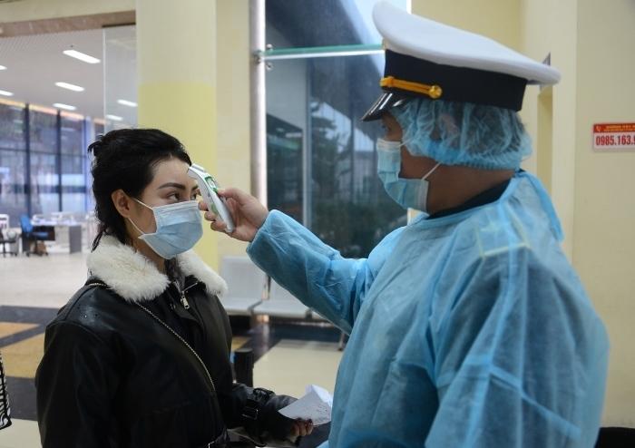 Cán bộ y tế đo thân nhiệt cho công dân tại Cửa khẩu quốc tế Móng Cái. Ảnh: Minh Cương