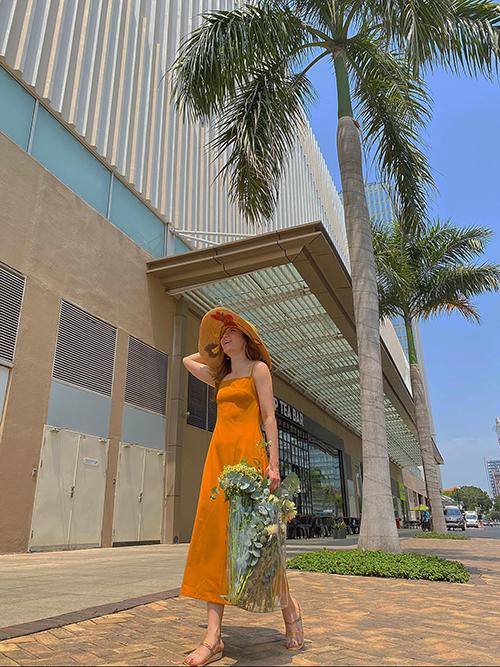 Váy hai dây với những tông màu thời thượng được Yến Nhi lăng xê vào đầu mùa hè. Phối cùng kiểu đầm đơn giản là mũ nan rộng vành, sandal đế cói.