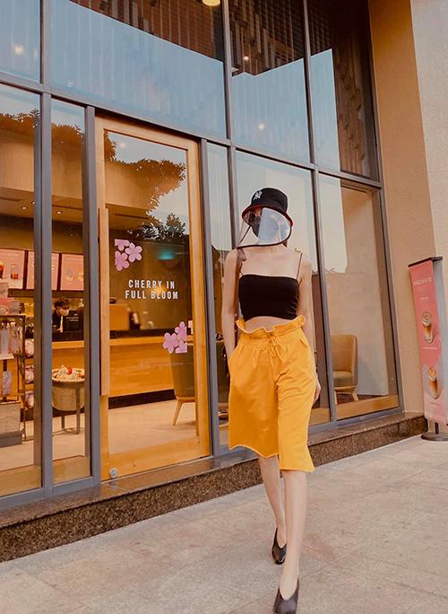 Trà Ngọc Hằng phối đồ trẻ trung với thiết kế áo hở eo, quần lửng dáng lưng cao và mũ bảo hộ khi xuống phố cafe.