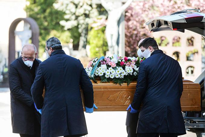 Các nhân viên nhà tang lễ di chuyển một cỗ quan tài tại nghĩa trang Bergamo. Ảnh: Reuters.