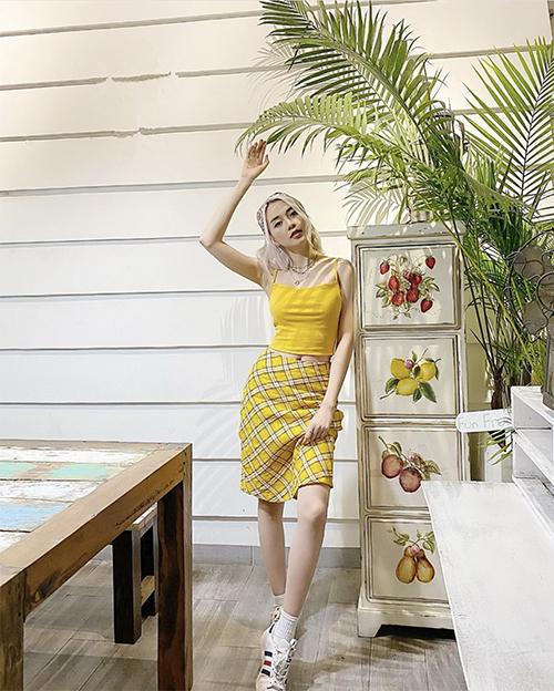 Tông vàng hot trend mùa hè được Thiều Bảo Trang mix-match bắt mắt với áo hai dây đi kèm chân váy ca rô.