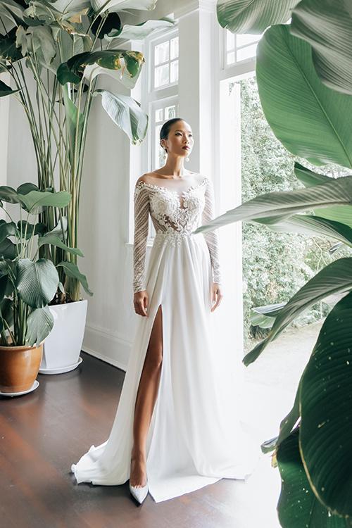 Váy cưới Letia có dáng A xoè nhẹ, cổ illusion cùng hoạ tiết thêu hoa nhỏ li ti, tay dài từ vải lưới ren. Mẫu váythể hiện đặc trưngtrong phong cách thiết kế của nhà mốt. Đó là tinh thần thời trang thanh lịch, chi tiết ren trang trí tinh xảo.