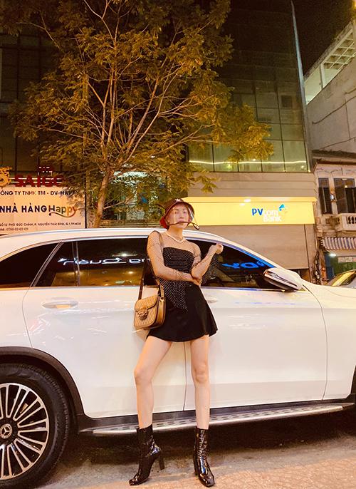 Khi phối áo lưới lấp lánh cùng chân váy ngắn, bốt da bóng, túi đeo chéo Gucci, Trà Ngọc Hằng vẫn mix thêm mũ chống dịch made in Việt Nam.