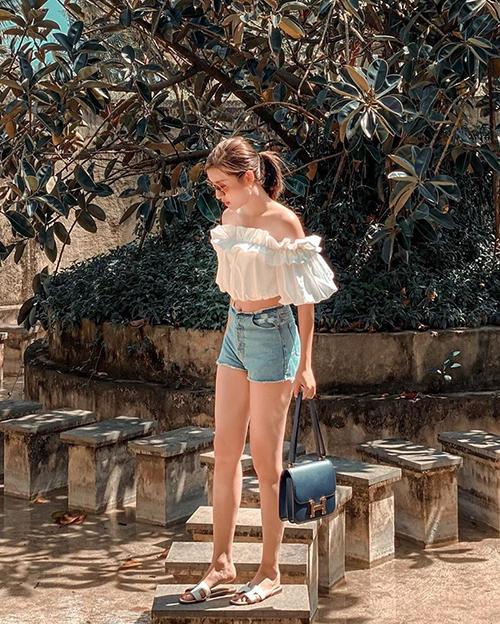 Khi đi trốn dịch vào mùa này, các nàng có thể tham khảo cách mix áo trễ vai trang trí bèo nhún đi kèm quần short jeans như á hậu Huyền My.