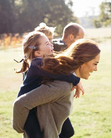 Kate cười tươi khi cõng con gái Charlotte bên cạnh chồng và con trai trên bãi cỏ. Ảnh: Kensington Palace.