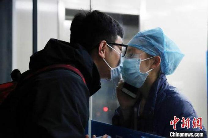 Nụ hôn qua cửa kính của Chen và Huang tại Bệnh viện tỉnh Chiết Giang hôm 4/2. Ảnh: Chinanews.