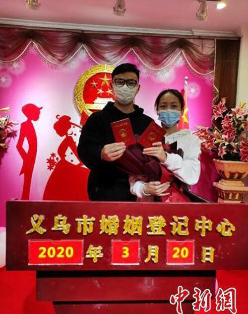 Chen vàHuang cầm giấy chứng nhận kết hôn sau khi đăng ký ở cục dân chínhthành phố Nghĩa Ô, tỉnh Chiết Giang hôm 20/3. Ảnh: Chinanews.