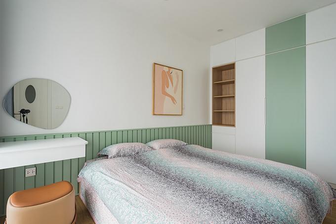 Phòng ngủ chính của gia chủ mang tông xanh xám đồng điệu với phòng khách. Điểm nhấn của căn phòng là tranh artwork và chiếc gương hình học.