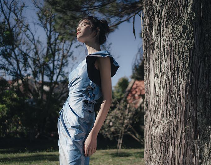 Nữ người mẫu chỉ trang điểm nhẹ, tóc búi cao và thoải mái dạo bước trong khu vườn tràn ngập cây xanh.