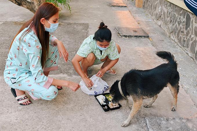 Võ Hoàng Yến và bạn cùng phòng dồn cơm thừa vào một hộp, trộn đều và mang cho chú chó trong khu cách ly tập trung.