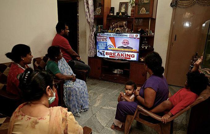 Một gia đình Ấn Độ theo dõi bài phát biểu của thủ tướng Narendra Modi trên truyền hình hôm 24/3. Ảnh: EPA.