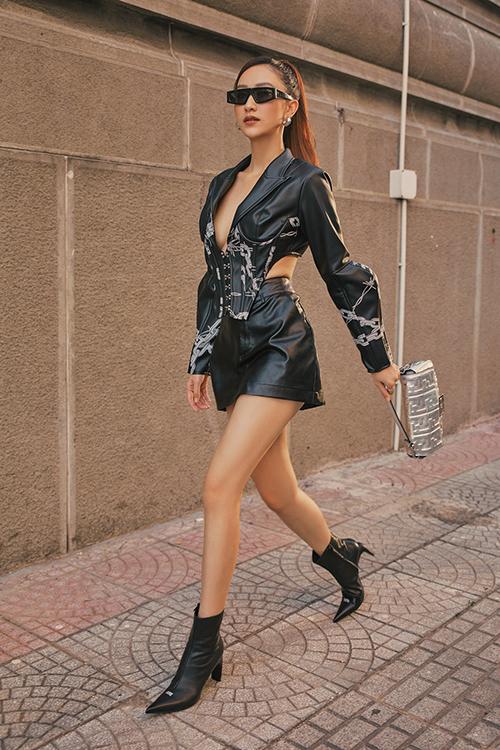 Jacket da biến tấu giữa kiểu corset và áo khoác cut-out mang tới kiểu trang phục độc đáo. Người đẹp chọn chân váy ngắn và bốt đồng màu để hoàn thiện set đồ.