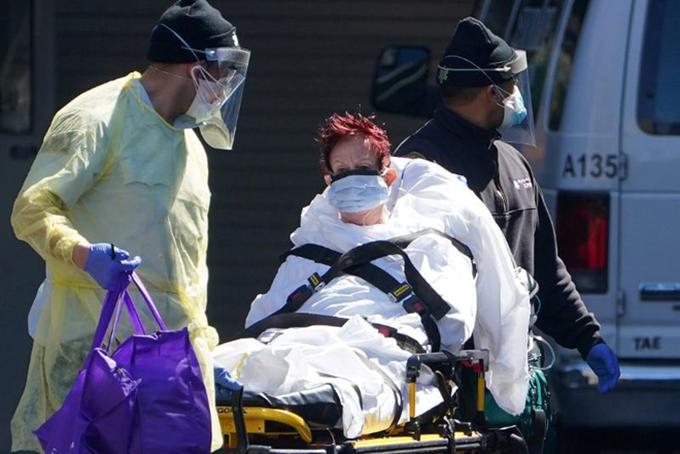 Một bệnh nhân Covid-19 được đưa đến xe cứu thương đưa đi tại quận Manhattan của thành phố New York, Mỹ hôm 26/3. Ảnh: Reuters.