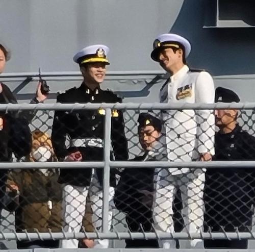 Lee Min Ho (phải) trò chuyện vui vẻ với bạn diễn trong lúc chờ đợi vào cảnh quay trên một con tàu của quân đội. Trong đoạn video ghi lại hậu trường, tài tử còn được bắt gặp cầm điện thoại chụp hình quang cảnh xung quanh.