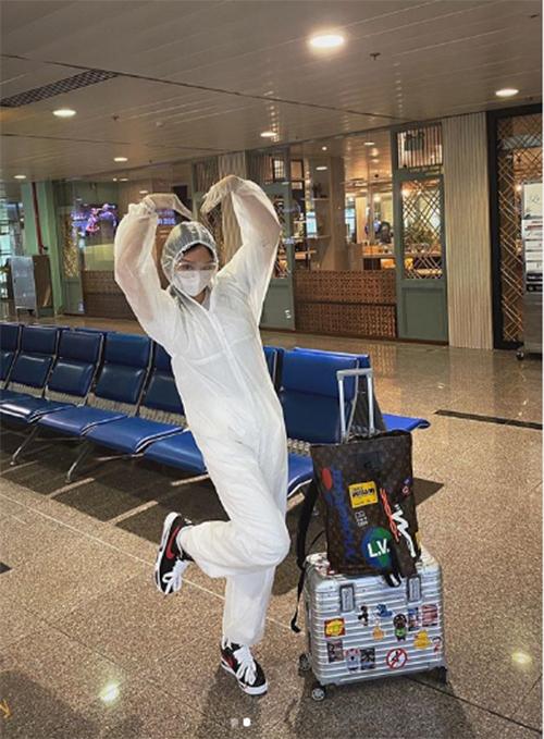 Miu Lê mặc trang phục bảo hộ khi đi máy bay.