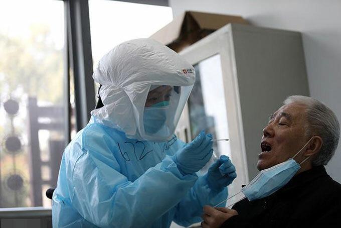Nhân viên y tế lấy mẫu xét nghiệm từ một bệnh nhân ở Vũ Hán, Trung Quốc hồi đầu tháng 3. Ảnh: Avalon.