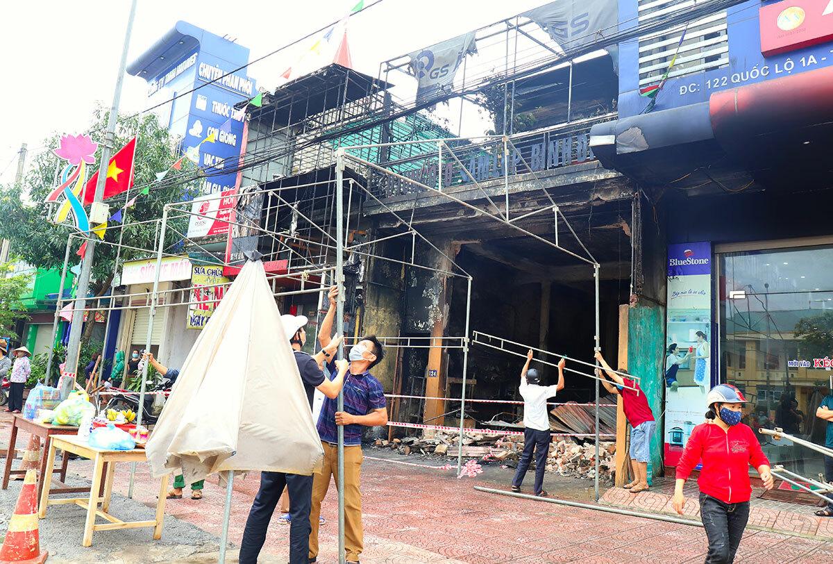Người dân dựng ra lo mai táng cho hai nạn nhân trước cửa hàng bị cháy. Ảnh: Hùng Lê