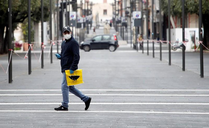 A man wearing a protective face mask walks on a street in Bari as the spread of the coronavirus disease (COVID-19) continues, in Bari, Italy, March 27, 2020.