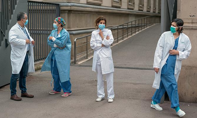 Các nhân viên y tế đứng bên ngoài một bệnh viện ở thành phố Barcelona, Tây Ban Nha. Ảnh: NYT.