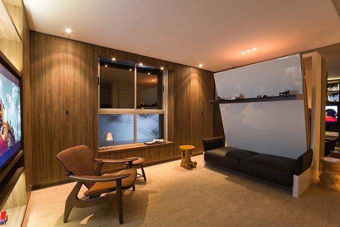 Chiếc ghế bành và ghế đẩu chiếm vị trí nổi bật trong không gian, giúp tạo điểm nhấn.Để tối ưu diện tích, gia chủ sử dụng chủ yếu nội thất đa chức năng. Chiếc giường gấp ẩn ngaysau bộ ghế sofa.