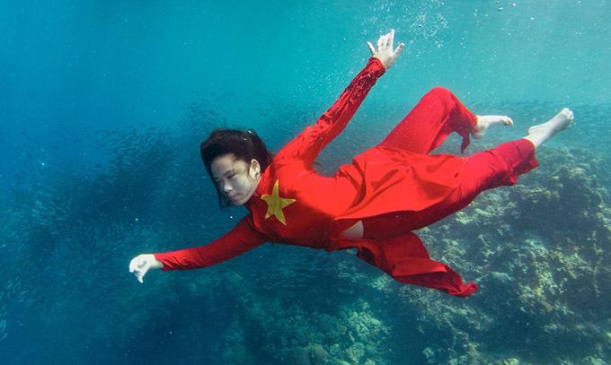 Bella Vũ ấn tượng với trang phục đỏ rực hoạ tiết cờ Tổ quốc. Mẫu 12 tuổi thích các loài sinh vật biển và có khả năng lặn sâu nên quyết định thực hiện bộ ảnh Vũ điệu đại dương làm kỷ niệm.