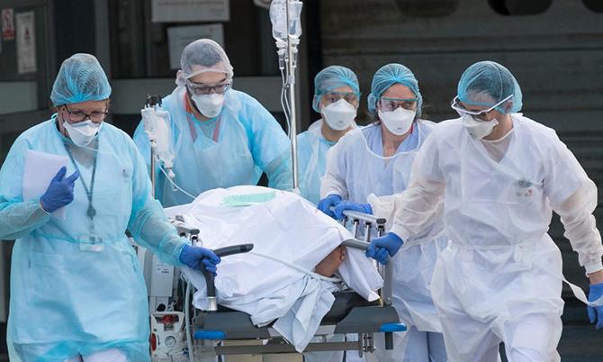 Các bác sĩ tại một bệnh viện ở Paris đang điều chuyển một bệnh nhân Covid-19. Ảnh: AP.