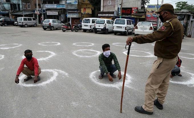 Cảnh sát Ấn Độ vẽ vòng tròn để người dân nhận biết khoảng cách tối thiểu với người khác khi ra đường. Ảnh: EFE.