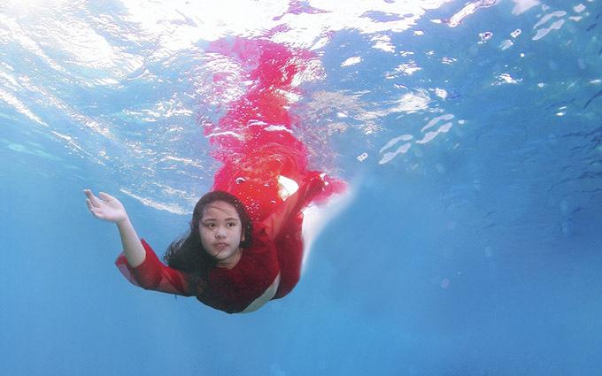 [Caption  Trước đây Bella đã hai lần chụp ảnh thời trang trong hồ bơi ở Việt Nam nhưng không ưng ý nên HLV Ngọc Anh gợi ý kết hợp cùng nhiếp ảnh gia Jun V Lao. Anh chàng người Phillippines nổi tiếng với những bức ảnh chụp dưới nước rất đẹp còn là huấn luyện viên lặn biển chuyên nghiệp. Từ đó bộ ảnh Vũ điệu đại dương ra đời trong lần nghỉ dưỡng cùng gia đình hồi đầu năm nay tại mũi Moalboal thuộc quần đảo Cebu. Đặc biệt Bella đã mang theo bộ áo dài in hình quốc kỳ Việt Nam và chiếc nón lá.  Buổi chụp hình trong một tiếng, từ lúc 11h – 12h để có được ánh nắng xuyên qua làn nước. Độ sâu 3 – 10m là nơi có thể tiếp cận đàn cá Sardine hàng triệu con. Bella Vũ không đeo bình khí mà sử dụng chung bộ cùm thở (một bộ cùm thở gồm 2 mồm thở, mồm thở chính và mồm thở phụ) với HLV. Ê kíp hỗ trợ buổi chụp là những HLV giàu kinh nghiệm hỗ trợ các hoạt động dưới nước cũng như cứu hộ nên việc an toàn luôn được đặt lên hàng đầu. Để chuẩn bị kĩ hơn cho lần chụp hình, cô bé đã học một khóa lặn tự do để tạo dáng và điều khiển cho chiếc váy xoè bồng bềnh lơ lửng trong môi trường không trọng lực không dễ dàng với dòng chảy dưới biển.