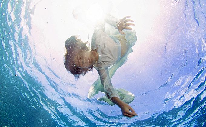 [CaptionBuổi chụp hình trong một tiếng, từ lúc 11h – 12h để có được ánh nắng xuyên qua làn nước. Độ sâu 3 – 10m là nơi có thể tiếp cận đàn cá Sardine hàng triệu con. Bella Vũ không đeo bình khí mà sử dụng chung bộ cùm thở (một bộ cùm thở gồm 2 mồm thở, mồm thở chính và mồm thở phụ) với HLV. Ê kíp hỗ trợ buổi chụp là những HLV giàu kinh nghiệm hỗ trợ các hoạt động dưới nước cũng như cứu hộ nên việc an toàn luôn được đặt lên hàng đầu. Để chuẩn bị kĩ hơn cho lần chụp hình, cô bé đã học một khóa lặn tự do để tạo dáng và điều khiển cho chiếc váy xoè bồng bềnh lơ lửng trong môi trường không trọng lực không dễ dàng với dòng chảy dưới biển.