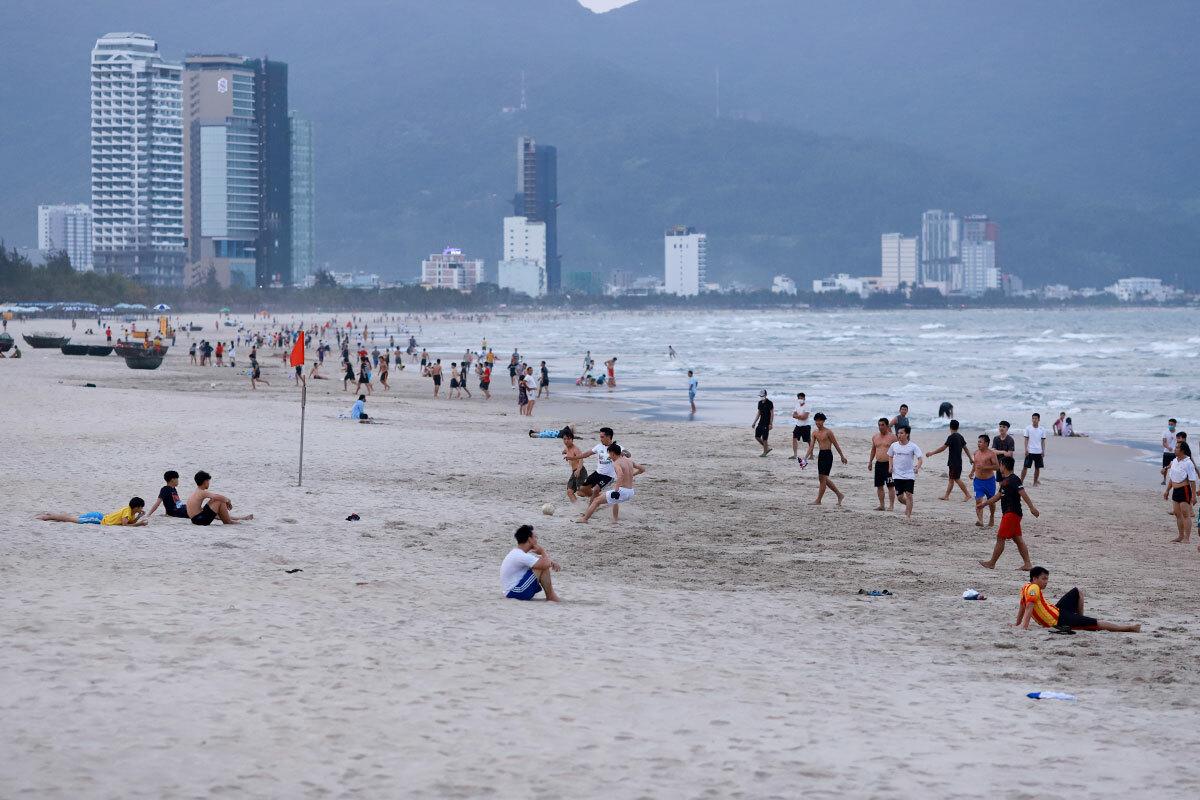 Người dân tắm biển, chơi thể thao trước bãi tắm Phạm Văn Đồng, chiều 29/3. Ảnh: Nguyễn Đông.