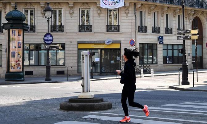 Một người dân Paris vẫn chạy bộ khi thành phố áp lệnh hạn chế đi lại hôm 27/3. Ảnh: AFP.