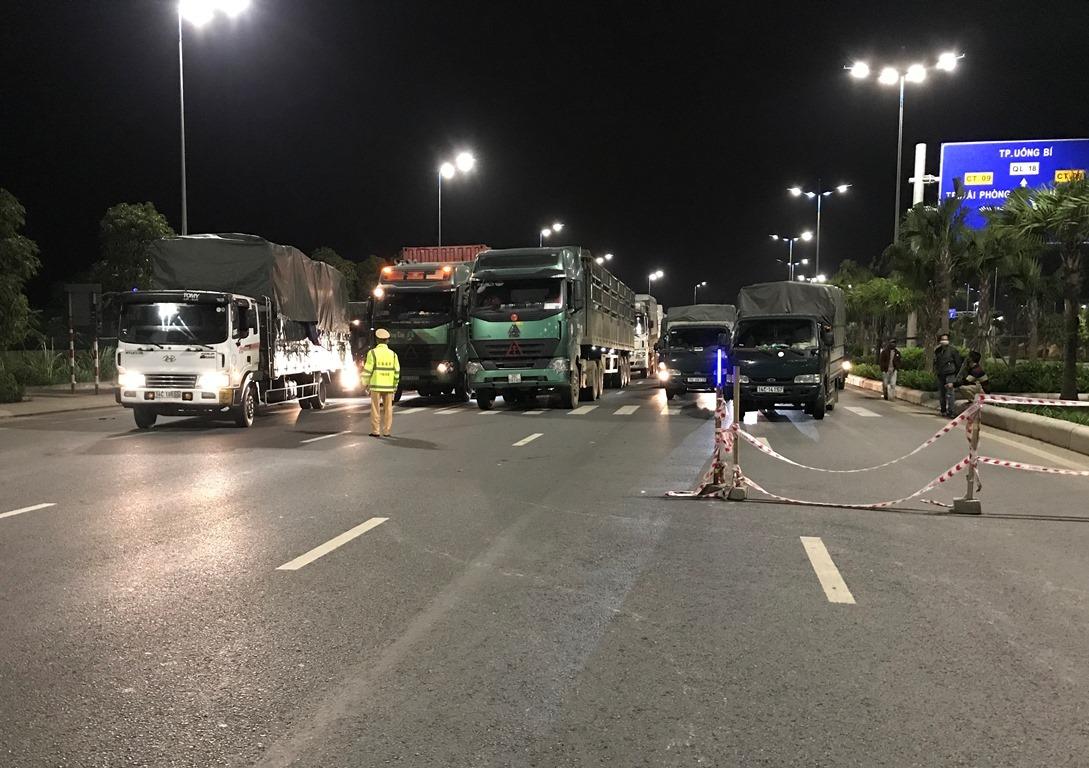 Tại điểm chốt trên quốc lộ 18A, phường Đại Yên, TP Hạ Long nhiều phương tiện nối đuôi nhau, tài xế xuống xe khai báo y tế, trình bày lý do. Ảnh: Minh Cương