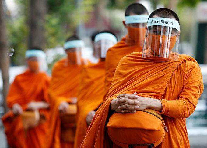 Các nhà sư Thái Lan đeo khẩu trang và mũ bảo hộ khi đi khất thực hôm 31/3. Ảnh: EPA.