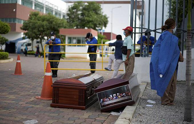 Cảnh sát và nhân viên nhà xác đưa quan tài đến thu gom các thi thể qua đời ở Guayaquil, Ecuador trong ba ngày qua. Ảnh: Reuters.