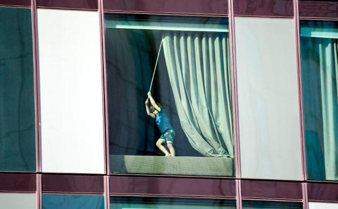 Đứa trẻ đang chơi đùa bên cửa sổ trong phòng cách ly ởMelbourne. Ảnh AFP